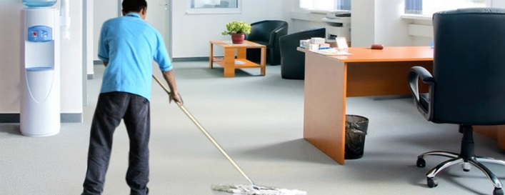 a man wearing blue shirt mopping the office floor