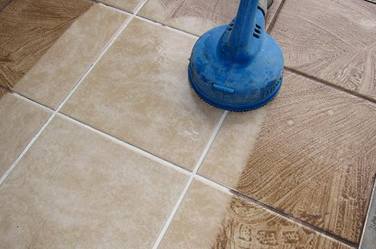 cleaning the dirty tiles using a blue cleaning equipment