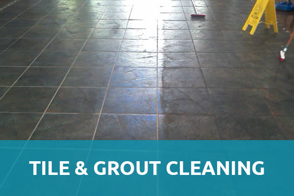 "A ceramic floor tiles with grout with the sun reflection and along with the floor cleaning materials and a yellow floor sign caution and a header title that says ""Tile & Grout Cleaning"" and that is one of the services of carpet cleaning Albuquerque."